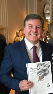 Mr Michael Gaunt holding a copy of Tatler magazine